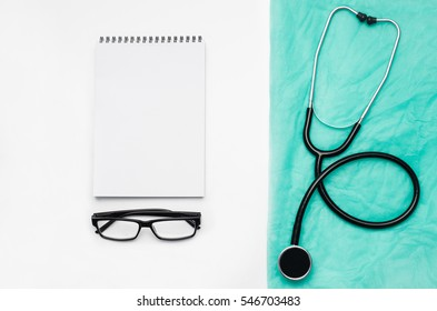 Top view of modern, sterile doctors office desk. Medical accessories on a white table background with copy space around products. Photo taken from above.