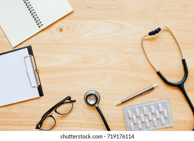 Top view of modern, sterile doctors office desk. Medical accessories on a wooden table background with copy space around products. Photo taken from above.