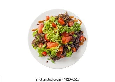 Top view of modern style smoked salmon salad with balsamic dressing in ceramic dish isolated on white background