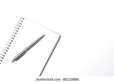 Top view of modern white office desk table with white notebook and pen with copy space, flat lay.
