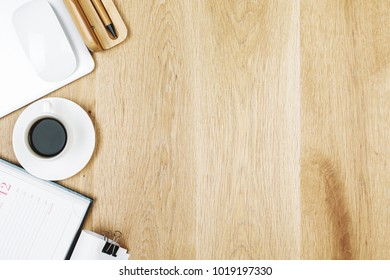 Top view of modern wooden office desk with various stationery tools, coffee cup and devices. Copy space