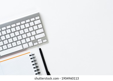 Top view of modern working place. Spiral notepad, pen and computer keyboard on white surface. Education, creativity and innovation concept with copy space. Digital technology in modern business.