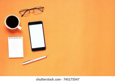 Top view, Modern workplace with notbook and pen with smart phone placed on white background. Copy space suitable for use in graphics.