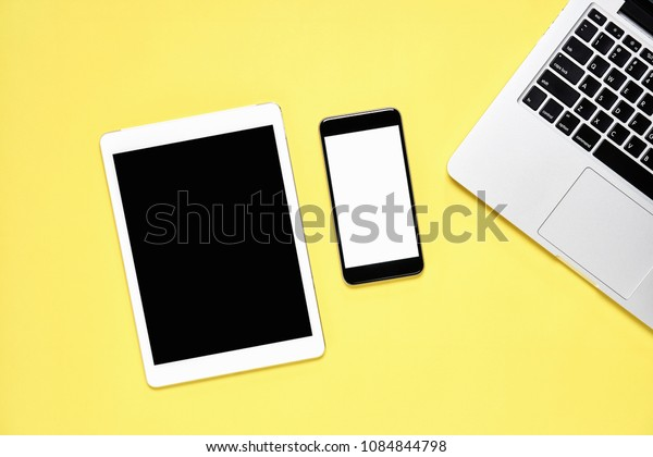 Top view, Modern workplace with tablet with smart phone placed on a pastel yellow background. Copy space suitable for use in graphics.