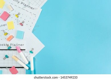 Top view of monthly and weekly planner with copy space, stationery and sticky notes on pastel blue background
