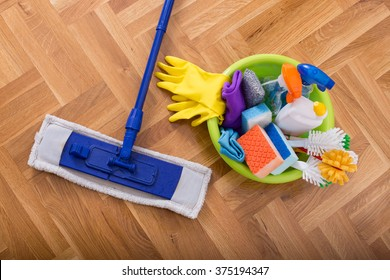 Top view of mopping stick and washbasin full of cleaning supplies and equipment on the parquet