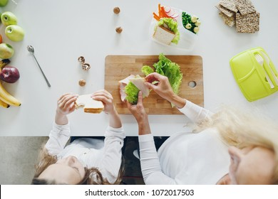 Top view mother with daughter preparing school snack or lunch in home kitchen