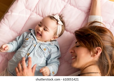 Top view of a mother and her adorable baby girl lying on the bed in bedroom, smiling and playing. Focus on the baby