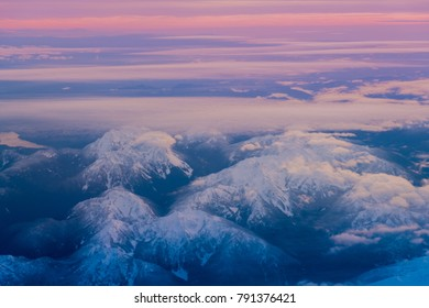 Top view of mountains with snow and clouds.