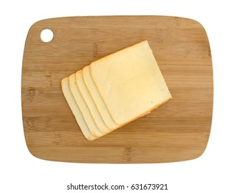 Top view of muenster cheese slices stacked on a wood cutting board isolated on a white background.