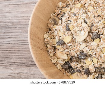 Top view - Muesli flake in wooden bowl on wooden background - Raw food ingredients