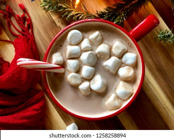 Top view of a mug of hot cocoa with marshmallows in a red mug on a wood surface