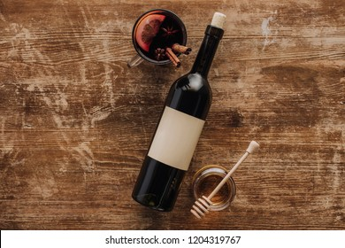 top view of mulled wine in cup, wine bottle and honey on wooden table