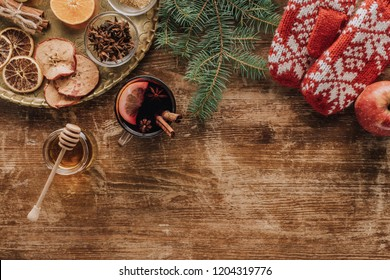 top view of mulled wine in cup, christmas fir twigs and mittens on wooden tabletop