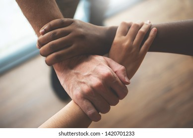 Top view of Multi ethnic business people holding their hands together. Unity. Community, Successful, teamwork, Assembling, Meeting. Diversity of African, American, Asian male and female team.