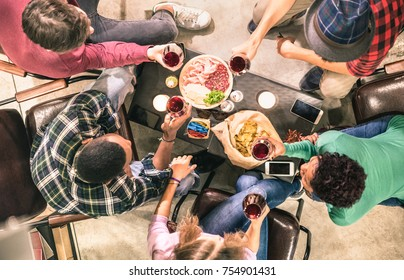 Top view of multi racial friends tasting red wine and having fun at fashion bar winery restaurant - Multicultural friendship concept with people enjoying time drinking together - Indoor neutral filter