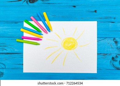 The top view of multi-color pencils with painted sun on white paper on blue wooden background