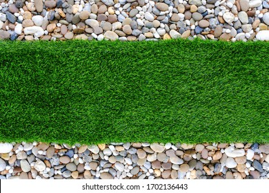 Top view of multi-colored pebble stones and artificial green grass for texture background. Decorative ground in the garden. Blank for text with copy space.