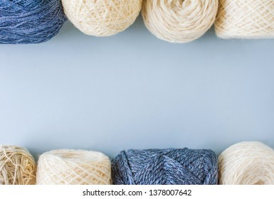 Top view of multi-colored woolen balls of yarn in a row on a blue background