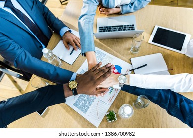 top view of multicultural businessmen and businesswomen putting hands together