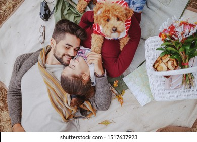 Top view of multicultural couple in love lying down on blanket, cuddling and holding dog. Picnic at autumn concept.
