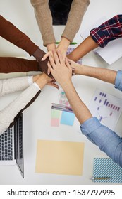 Top view of multi-ethnic business team staking hands over meeting table in office, copy space