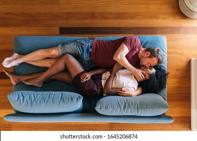 Top view of multiethnic couple lying on blue couch in front of each other and kissing at home