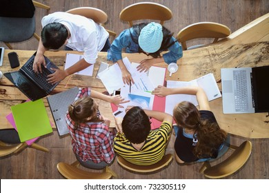Top view of multiethnic diverse group of young college students brainstorm discussion about medical document and search data on laptop, co-working education teamwork concept