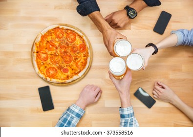 Top view of multiethnic group of young people drinking beer and eating pizza