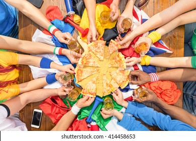 Top view of multiethnic hands of football friend supporter sharing pizza margherita - Friendship concept with soccer fan enjoying food together - People eating at party bar pub after sport match event