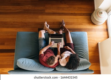Top view of multiethnic young couple in casual clothing sitting on comfortable blue sofa and watching video on laptop at home