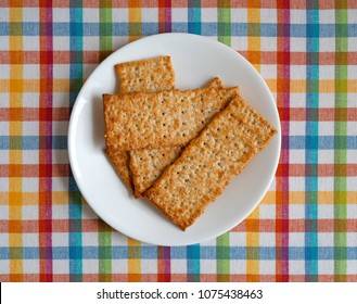Top view of multigrain flatbread crackers on a white plate atop a colorful place mat.