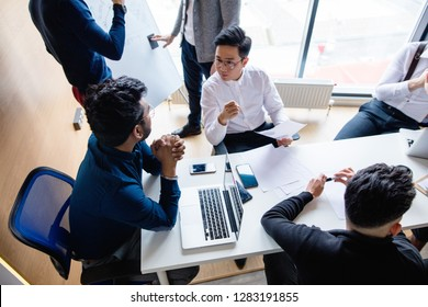 Top view of multiracial creative business men in white and black formal clothes disputing at a meeting using gadgets during the conference while sitting at the modern office.