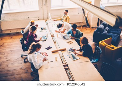 Top view of multiracial group of students have training lesson in classroom using technology, crew of creative designers collaborating during brainstorming session in coworking office sitting at table