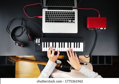 Top view of music composer playing MIDI keyboard and electric guitar to create music at home studio.