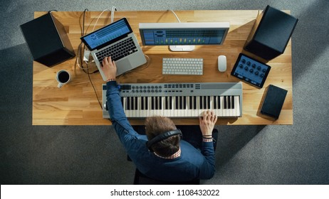 Top View of a Musician Creating Music at His Studio, Playing on a Musical Keyboard. His Studio is Sunny and Pleasant Looking.