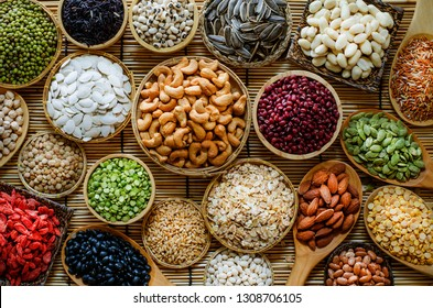 Top view of natural and cereal food consisted of cashew nut,sunflower and pumpkin seed,green,red,back bean,soybean,almond,goji berry,lentils,rice,peanut,millet,and oat,in hard color and low key tone