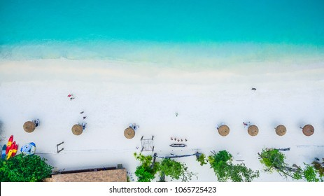 Top view of natural clear blue sea and white sand beach with umbrella , Andaman sea, South of Myanmar and Thailand, Top view from drone, Beautiful destination place Asia, Summer vacation travel trip