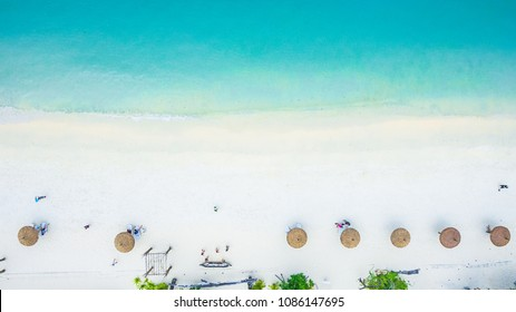 Top view of natural clear blue sea and white sand beach with umbrella, Andaman sea, South of Myanmar and Thailand, aerial view from drone, Beautiful destination place Asia, Summer vacation travel trip