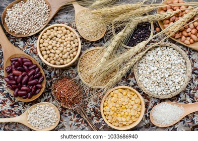 Top view of natural grain seeds consisted of dry red and soybean, peanut, wheat, rice, and millet put in wooden equipment on grunge vintage woden background, decorated by dry wheat