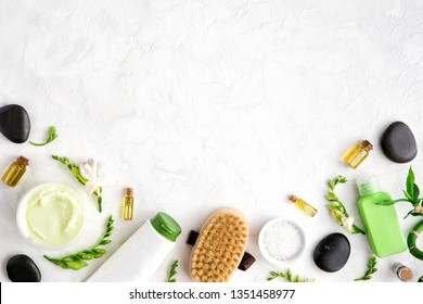 Top view of natural skincare and spa cosmetic products on white marble table, flat lay. Frame of cream, oil, sea bath salt, massage brush, bamboo and flower buds. Beauty flatlay concept