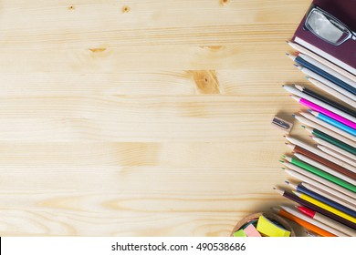 Top view of natural wooden desktop with colorful supplies. Mock up