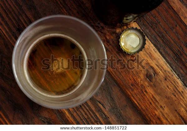 Top view of near empty beer glass with bottle cap and bottle on rustic wood background.  Low key still life with directional natural lighting for effect.  Selective focus on bottle cap and droplet.