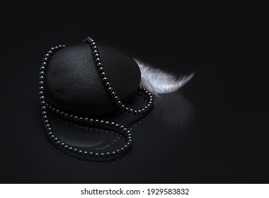 A top view of a necklace made of black pearls on black background with a white feather on the side