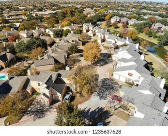 Top view new condo and townhome communities near Dallas, Texas, USA with colorful fall foliage. Townhouse complex at suburban neighborhood near canal. Tightly packed homes housing and driveway