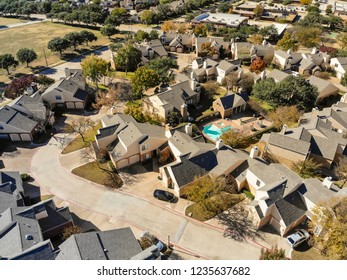 Top view new park side condo and townhome communities near Dallas, Texas, USA with colorful fall foliage. Townhouse complex at suburban neighborhood. Tightly packed homes housing and driveway