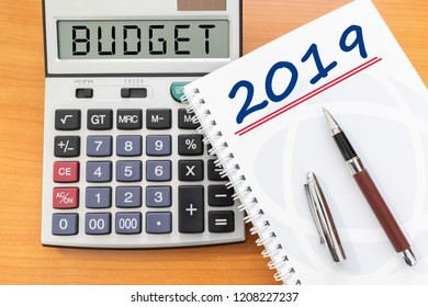 Top view of new year 2019 budget on calculator sign with pen on wooden table. Financial planning