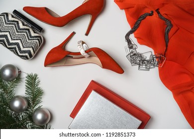 Top view to new year and christmas party outfit composition red shoes accessories jewelry clutch fir tree with balls white background. Party date night conception. Flat lay, copy space