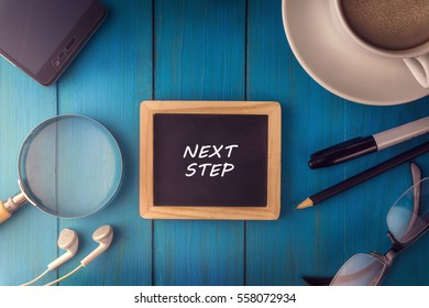 Top view of NEXT STEP written on the chalkboard,business concept.chalkboard,smart phone,cup,magnifier glass,glasses pen on wooden desk.