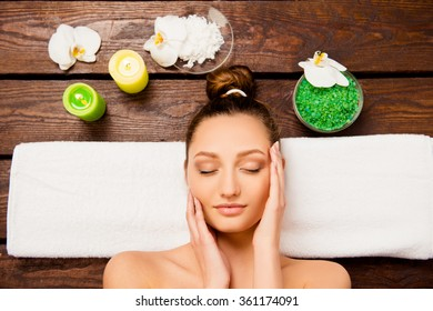 Top view of nice young woman laying in spa salon relaxing with closed eyes
